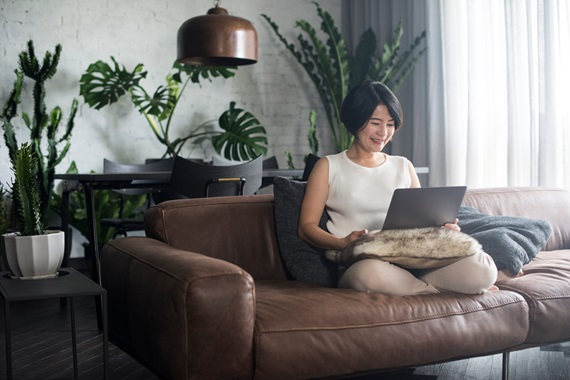 Female sitting on sofa with laptop