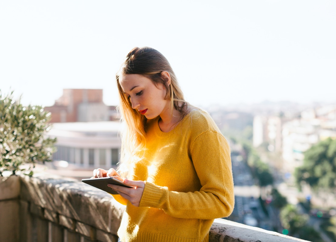 Woman on tablet standing outside