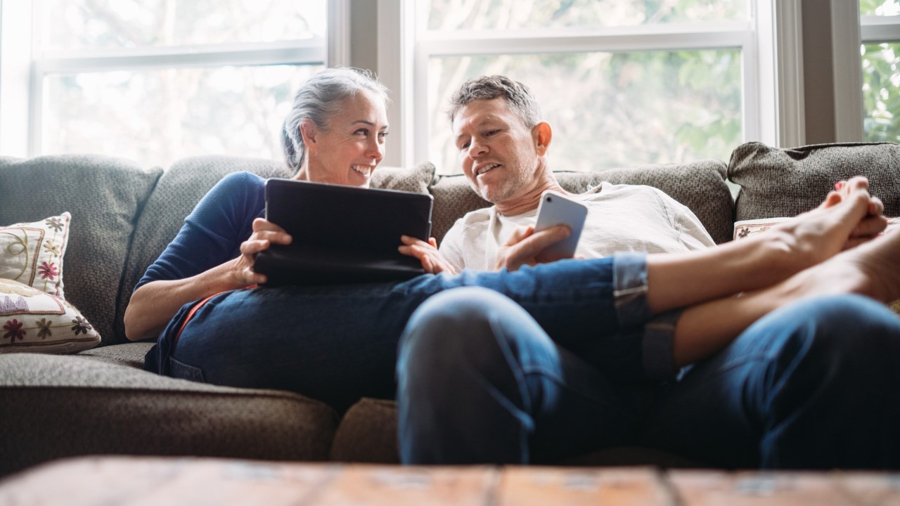 Older man and woman looking at laptop on couch