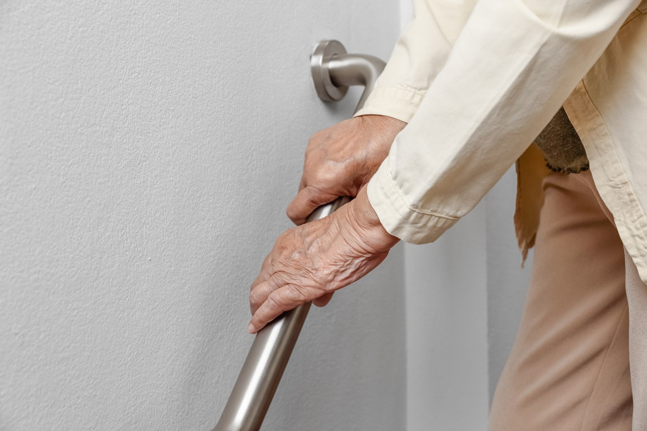 Elderly person leaning on hand rail