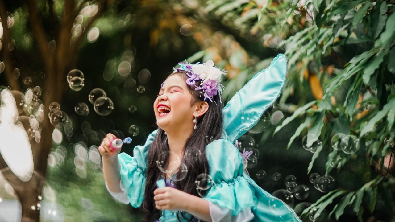 Young girl in fairy costume laughing and blowing bubbles