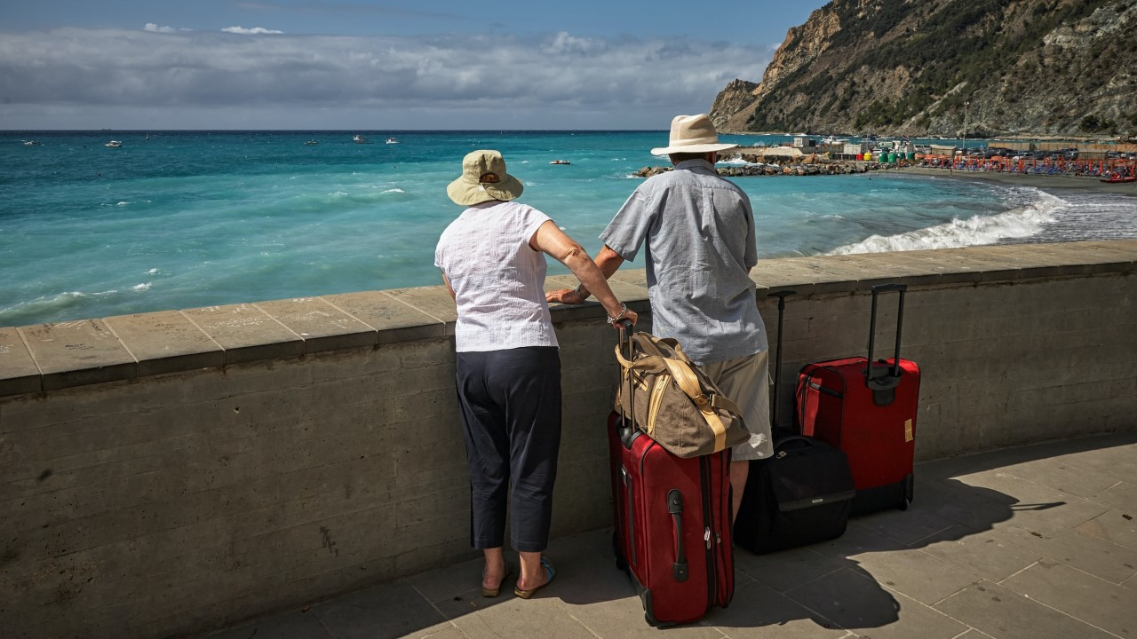 Older man and woman with suitcases looking out over a beach